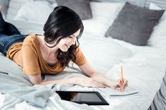 Romantic girl lying on her bed. Creating poem. Cheerful brunette woman expressing positivity while making notes and thinking about him royalty free stock images