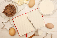 Creating a Recipe. Directly above view of blank recipe book with various ingredients. Add own text Stock Image