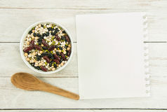 Creating a Recipe. Directly above view of notebook and cereal bowl around it Royalty Free Stock Photos