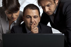 Creating a strategy. Three serious business people over a laptop thinking Stock Photos