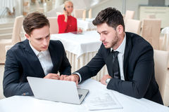 Creating a strategy. Two successful and confident businessman si. Tting at the table in a business office in full costume in the office and working at a laptop Royalty Free Stock Image