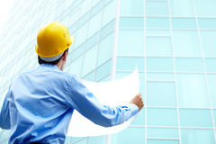 Creation. Rear view of architect looking comparing housing project with building Royalty Free Stock Photo