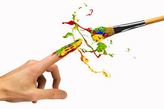 Creation between hand and paintbrush. Creation of color between hand and paintbrush Royalty Free Stock Images