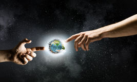 Creation concept. Close up of human hands touching with fingers. Elements of this image are furnished by NASA Stock Photography
