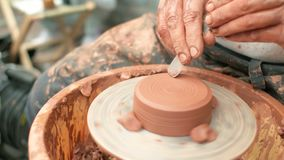 Creation covers a clay pot. Close up of hands working clay on potter`s wheel stock video