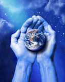 Creation Earth Hands Science Climate. A pair of hands holding planet earth with a stars and clouds background Stock Photos