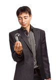 Creation of idea. Young man in business suit holds light bulb isolated on white background Royalty Free Stock Photo
