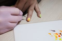 Creation of a manicure with a pattern in the Easter style. A woman creates a tassel of a manicure in an Easter style in yellow with a tassel Stock Image