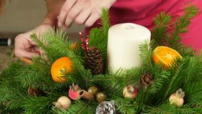 Creation of a table Christmas composition. Transition frame with Christmas toys on a candlestick of spruce, cones and. Tangerines stock footage