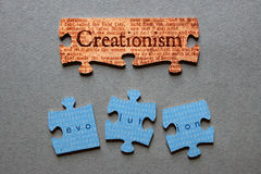 Creationism Matched and Evolution Mismatched Jigsaw. Creationism against background of Genesis text printed on matched jigsaw pieces with Evolution against Royalty Free Stock Image