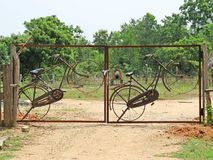 Creativ gate in Auroville. Bicycles fit into a gate in Auroville royalty free stock images