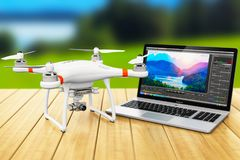 Quadcopter drone and laptop with video software outdoors. Creative abstract 3D render illustration of the black professional quadcopter drone and laptop of Royalty Free Stock Image