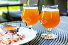 Two glasses of beer and meat snacks. Creative abstract macro view of two glasses of fresh cold light beer and meat snacks outdoors with selective focus effect Stock Images