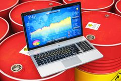 Laptop with stock exchange market app on red oil drums Royalty Free Stock Photo