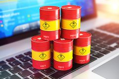Red oil drums on laptop with stock exchange market app. Creative abstract oil and gas industry manufacturing and internet web online trading commercial business Stock Photography