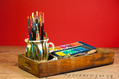 Creative activity painting supplies brushes colors in wood box vintage look. Colorful stock photo