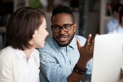 Creative african american and caucasian workers discussing work chatting. Friendly diverse colleagues having conversation in office, creative african american stock photography