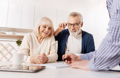 Creative agent showing house layout to aged couple of clients Royalty Free Stock Image