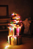 Creative alternative tree of books and colored garlands. Christmas lights. Mannequins, frames in the background.