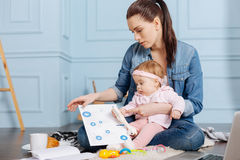 Creative ambitious mother developing some ideas. With a little helper. Graceful focused inventive women thinking about new projects while analyzing data and stock photo