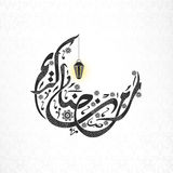 Creative Arabic text for Ramadan Kareem celebration. Creative Arabic Islamic calligraphy of text Ramadan Kareem in crescent moon shape with hanging lantern on Stock Photo