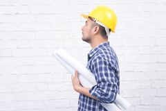 Creative architect or engineer holding blueprint rolls wearing y royalty free stock images