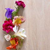 Creative arrangement made of different flowers on wooden background with space for text. Royalty Free Stock Photos