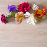Creative arrangement made of different flowers on wooden background with space for text. Stock Photos