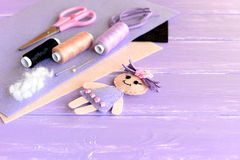 Creative art and craft idea for children. Felt doll, scissors, thread, needles, pins, suede cord, felt sheets on wooden background Stock Photography