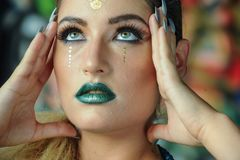 Creative art makeup of a young girl with green eyes. Royalty Free Stock Photography
