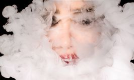 Creative of art woman portrait and smoke in face. portrait and smoke on black background. stock photography