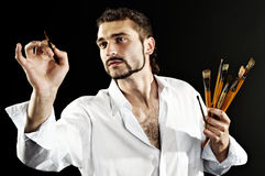 Creative artist in action. Artist in a white shirt on a black background with a brush. contrast shot Royalty Free Stock Photos
