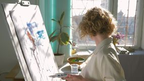 Creative artist inspiration, happy craftsman woman with muse paints picture with bright colors on white canvas on easel. Indoors, shooting in motion stock footage