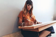 Freelance illustrator working from home. Creative artist making an illustration sitting on floor. Illustrator making a free hand drawing royalty free stock photography