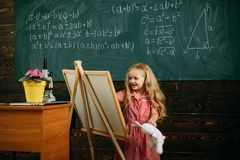Creative artist painting on studio easel. Little artist girl creating picture in class.  stock photos