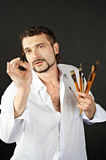 Creative artist with palette and brushes looks ahead. Creative artist in a white shirt on a black background with a brush Stock Image