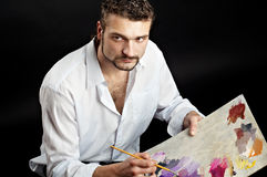 Creative artist with palette and brushes looks toward. Artist in a white shirt on a black background with a brush. Makes the outline of the palette. glance at Royalty Free Stock Images