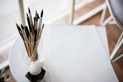 Creative artist's workspace, artistic paint brushes and paper. Creative artist's workspace, artistic paint brushes and clean paper in studio interior, painting royalty free stock photos
