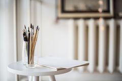 Creative artist's workspace, artistic paint brushes and paper. Creative artist's workspace, artistic paint brushes and clean paper in studio interior, painting stock images