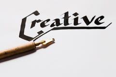 Creative artist workplace. Writer inspiration. Ink handwritten word and pen top view. Painter workshop, art, literature, creativity, handmade drawing concept Stock Photos