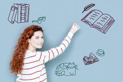 Creative author looking inspired while writing a new book. Talented author. Positive talented young writer looking happy while working at the new book Royalty Free Stock Photo