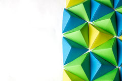 Creative background with blue, green and yellow origami tetrahedrons Stock Photo