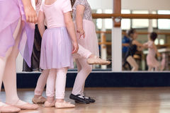 Creative Ballet Close Up little girls in ballet slippers with one girl kicking foot out; mirror in background royalty free stock photo