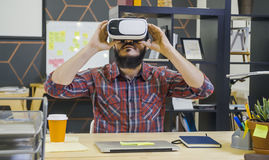 Creative bearded man uses virtual reality glasses. At his desk in office stock photos