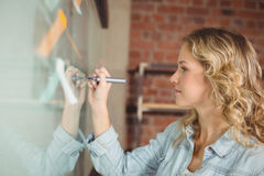 Creative beautiful businesswoman writing on board in office Stock Photos