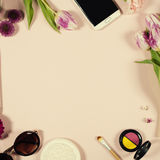 Creative beauty feminine arrangement of flowers and cosmetics Stock Photos
