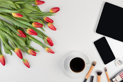 Creative beauty feminine background with flowers, coffe and make up tools, cosmetics. Top view Stock Image