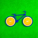A creative bicycle with wheels in the form of oranges. The style. A creative bicycle with wheels in the form of oranges. Bright green background. Illustration in Royalty Free Stock Image