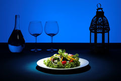 Creative Blue Salad. Salad plate with blue background and glasses in silhouette Royalty Free Stock Images