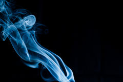 Creative blue smoke on black background. Creative unique silky curve shape smoke on isolated black background Royalty Free Stock Images